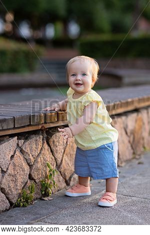 Portrait Of Cute Little Caucasian Baby Girl Ten Months Old Playing In Summer Park. Stylish Infant Wi