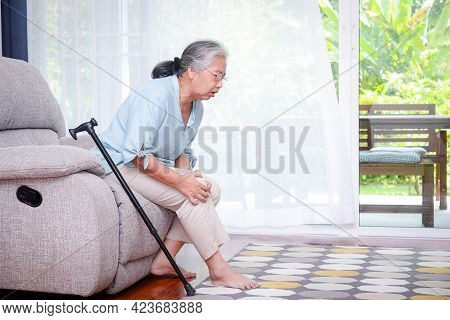 Asian Elderly Woman Sitting On The Sofa In The House, There Was A Walking Stick Nearby. And Had Knee