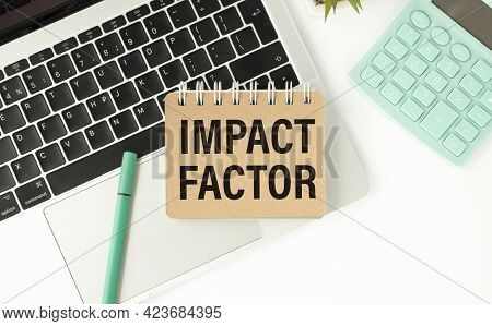 Businessman Holding A Card With Text Impact Factor. Keyboard, Calculator And White Background