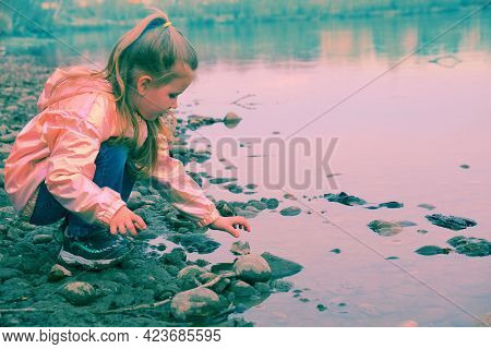 Child Girl Standing On Stones Rock In Natural Stream In Springtime Or Autumn  And Playing With Stone