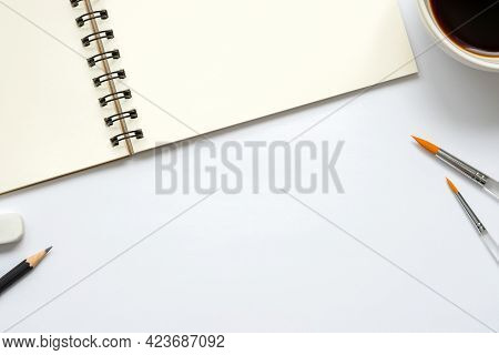 Open Blank Notebook With A Cup Of Coffee, Paintbrush, Pencil And Eraser On White Background, Copy Sp