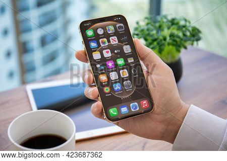 Alanya, Turkey - April 7, 2021: Man Hand Holding Iphone 12 Pro Max Gold With Home Screen Ios 14 On T
