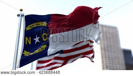 The Flags Of The North Carolina State And United States Of America Waving In The Wind. Democracy And