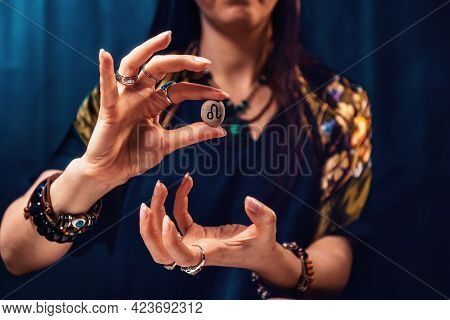 Astrology And Horoscope. A Woman Holds A Stone With The Sign Of The Zodiac Leo. Close Up. The Concep
