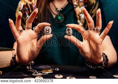 Astrology And Horoscope. Female's Holds Stones With The Zodiac Sign Of Taurus And Sagittarius. The C