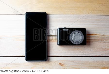 Overhead Shot Of A Compact Photographic Camera On A Wooden Table Next To A Smartphone. Mobile Photog
