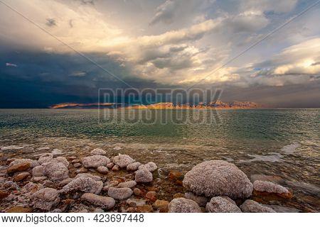 Israeli coast. Rocky beach covered with evaporated salt. The Dead Sea, sunset. The sun illuminates the Jordanian coast. Gloomy sky with dark thunderclouds.