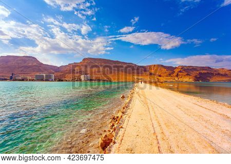The landfill embankment runs through the sea. After a thunderstorm. Israel, legendary Dead Sea. The smooth surface of the salty sea reflects the sky and clouds.
