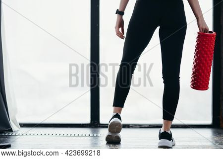 Back Photo. Girl In Black Leggings Holds Fascia While Standing On The Background Of Windows