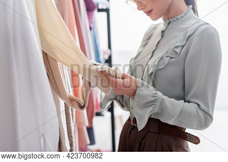 Cropped View Of Seamstress Touching Clothes In Atelier.
