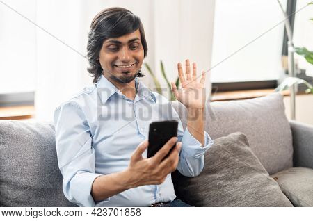 Pleased Young Indian Man Has Video Call On The Smartphone Sitting On The Couch At Home, Chatting Wit