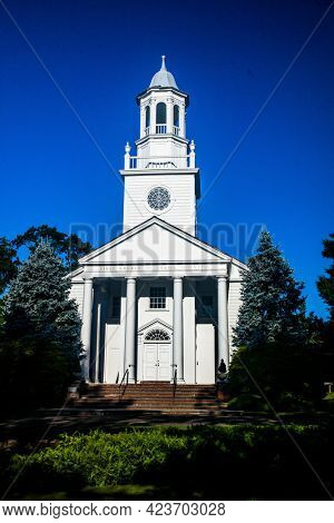 NEW CANAAN, CT, USA- JUNE 13, 2021:  First Church Of Christ, Scientist with morning sun and blue sky view from Park Street