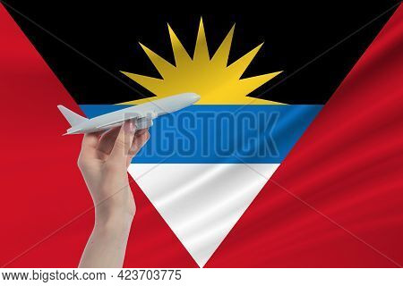 Airplane In Hand With National Flag Of Antigua And Barbuda. Travel To Antigua And Barbuda.