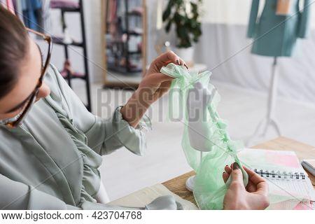 Blurred Designer Holding Fabric Near Mannequin In Designer Studio.