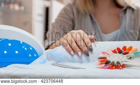 Woman With Artificial Acrylic Nails Picks Up New Polish Color During Manicure Procedure. Manicure Pr