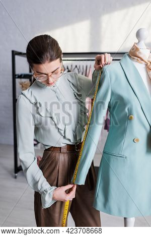 Designer Measuring Sleeve Of Blazer On Mannequin While Working In Atelier.