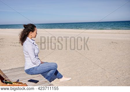Serene Brunette Woman Sitting On A Wooden Chaise Lounge And Enjoying The Tranquil View To The Seasho