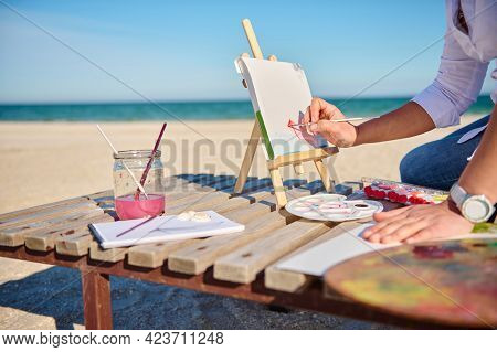 Cropped Image Of An Artist's Hand Holding Paintbrush And Painting Boat With Watercolors, Sitting On