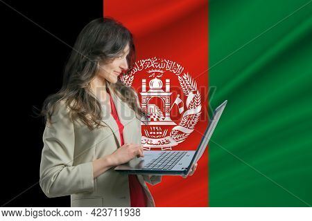 Freelance In Afghanistan. Beautiful Young Woman Freelancer Uses Laptop Computer Against The Backgrou