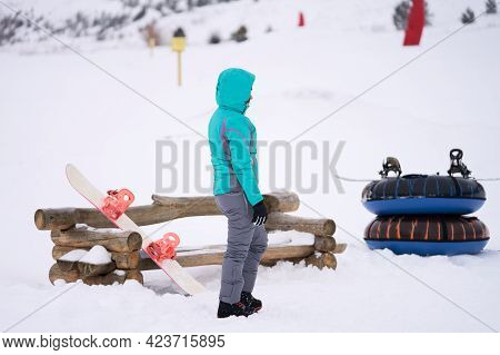 A Female Novice Snowboarder Is Waiting For An Instructor At The Mountainside. She Put Her Snowboard