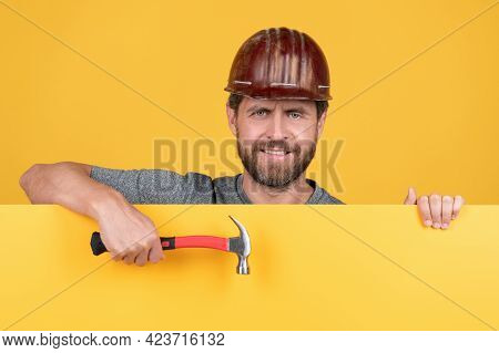 Happy Mature Man Laborer In Helmet Behind Yellow Paper For Copy Space Hold Hammer, Happy Workers Day