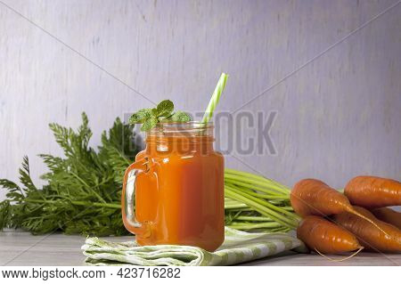 Delicious And Healthy Juice Of Young Carrots. Orange Drink. Carrot Juice. Fresh Carrots With Green L