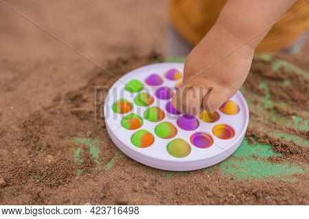 Colorful Antistress Sensory Toy Fidget Push Pop It In Toddlers Hands. Antistress Trendy Pop It Toy.