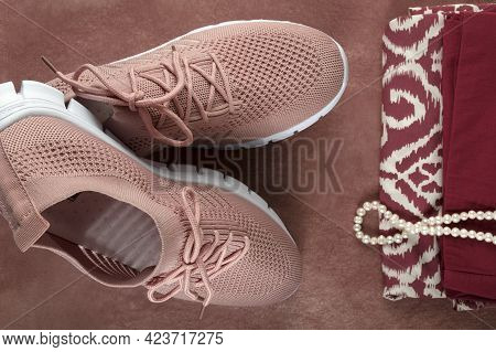 Pink Women's Shoes Made Of Light Soft Fabric. The Shoes Lie On A Light Brown Background With Trouser