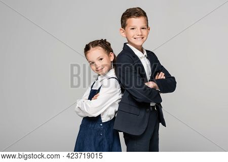 Happy Schoolchildren In Uniform Posing With Crossed Arms Isolated On Grey