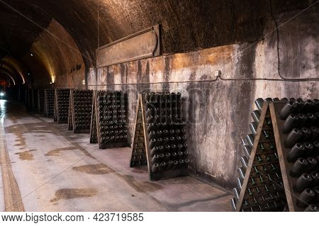 Champagne Sparkling Wine Production In Bottles In Racks In Underground Cellar, Reims, Champagne, Fra