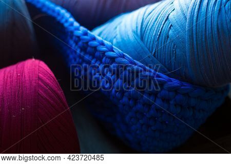 Two Skeins Of Yarn In Knitted With Hook Basket. Blu, Indigo And Burgundy Threads. Knitted Fabric. Ha