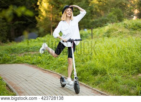 Cheerful Beautiful Girl In Black Hat And White Shirt Riding An Electric Scooter In Urban Style In Su