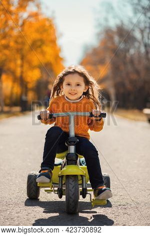 Portrait Of A Little Cute Girl On A Bike In The Morning Autumn Park.