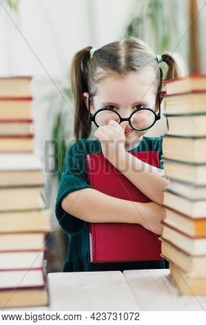 Cute Little Girl In Green Dress With Red Book In Her Hands Fixing A Glasses On Her Nose. Reading And