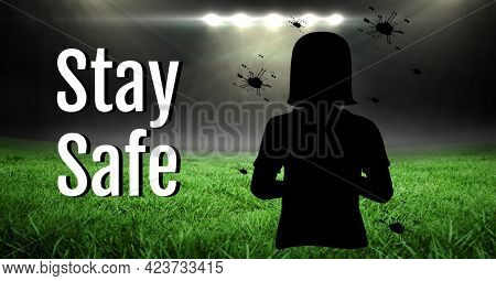 Composition of stay safe text and covid 19 cells with girl silhouette over sports stadium. sports and competition during covid 19 pandemic concept digitally generated image.