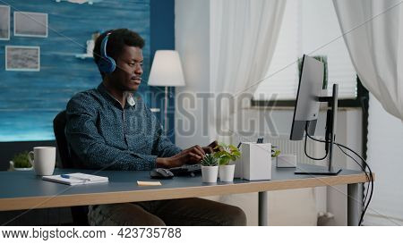 Black Man Using Headphones To Listen Music While Working From Home Office On The Computer. Young Fre