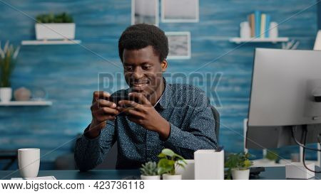 African American Man Playing Video Games On His Phone, Smiling And Enjoying Leisure Time. Mobile Ent