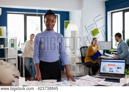 Black Woman Entrepreneur Looking At Camera With Business People Working On Project Strategy. Diverse