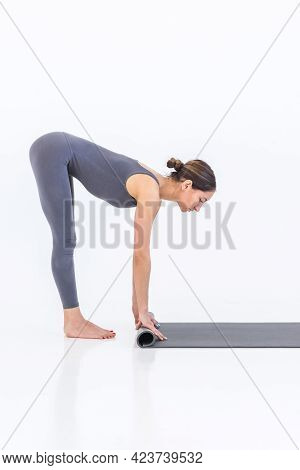 Beautiful Sportive Woman Yoga Trainer Unrolls Or Rolls Up A Carpet