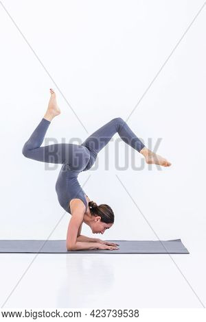 Beautiful Sportive Woman Doing Yoga Practicing A Pose Standing On Her Hands On A Mat On A White Back