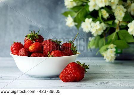 Ripe Strawberries In White Plate And Jasmine Flowers