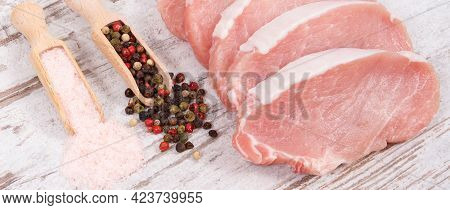 Slices Of Fresh Raw Loin With Pepper And Salt On Wooden Spoons For Cooking