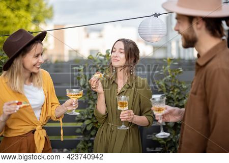 Young Friends Spending Summertime Together, Standing With Drinks And Snacks On A Backyard Of The Cou