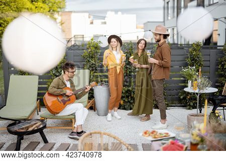 Friends Hang Out Together On A Beautiful Cottage Backyard, Playing On A Guitar, Playing With A Dog A