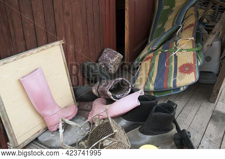 Pile Of Discarded Footwear Along With Collection Of Used Household Stuff In A Storage Room