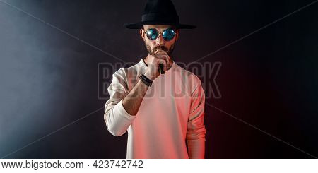 Stylish Man In Sunglasses Puffing The Vapor On The Black Background