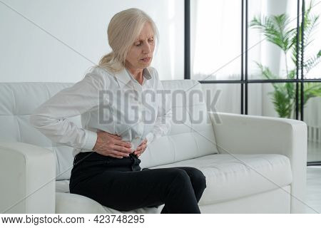 An Elderly Woman Suffers From Abdominal Pain, A Mature Elderly Adult Woman Feels Abdominal Pain Whil