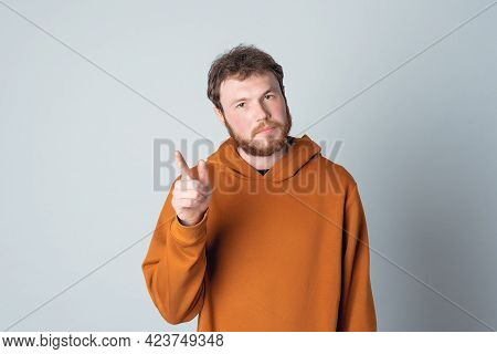 Serious Bearded Modern Young Man With Attention Gesture. He Holding Finger Up, Warning Listen To Me