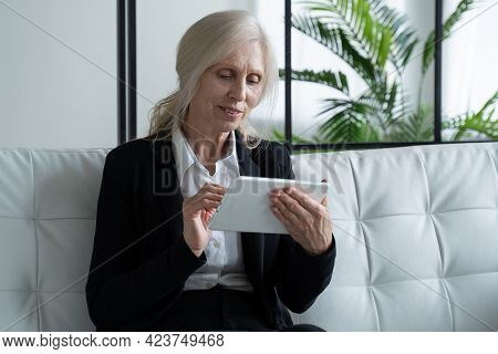 Elderly Woman Uses A Digital Tablet While Sitting On The Couch At Home. The Use Of Technology By Old