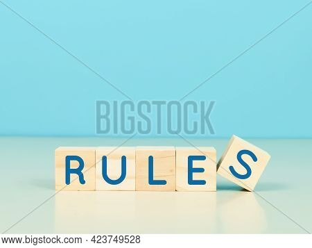 Rules And Regulations Concept. Wooden Cubes Written Rules On Blue Background.